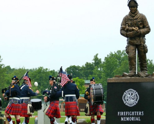 Bag pipers performing next to firefighters memorial of bronze statue of fireman carrying a baby
