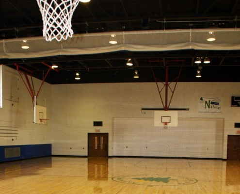 Basketball net in the foreground and view of volleyball curtain and two other basketball courts in the Beech Acres Park RecPlex Gym