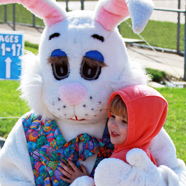 child hugs the easter bunny at Youth Egg Hunts