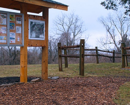 Start of a trail Johnson Hills Park. A informational bulletin board stands in front of it