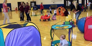 gym full of toys, kids and parents at preschool open gym