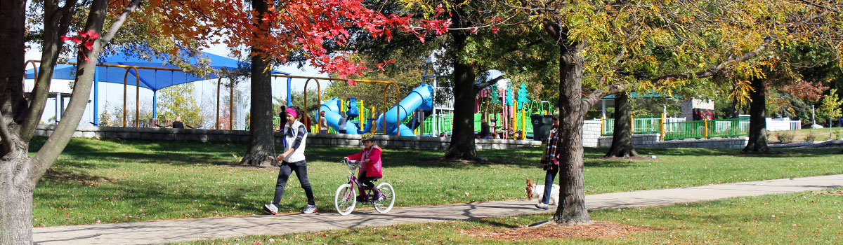 park patrons walking on the trail at juilfs park. Playground is in the background