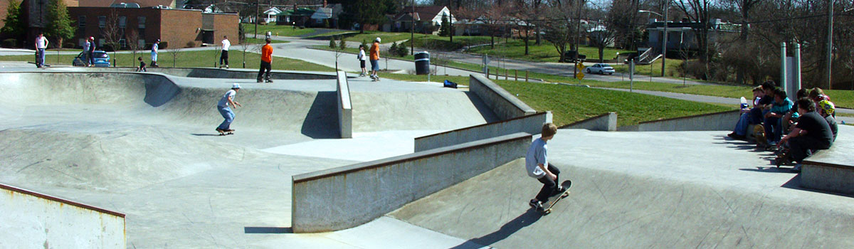 Spectators and skateboarders enjoying the warm weather at the skatepark