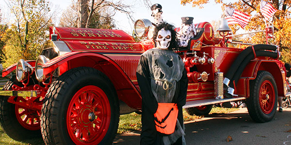 trunk 'r treak fall festival classic fire truck and kid in costume