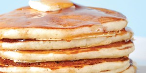 closeup of stack of pancakes with butter and syrup