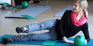 instructor teaching park district pilates mat mix on a mat with a ball