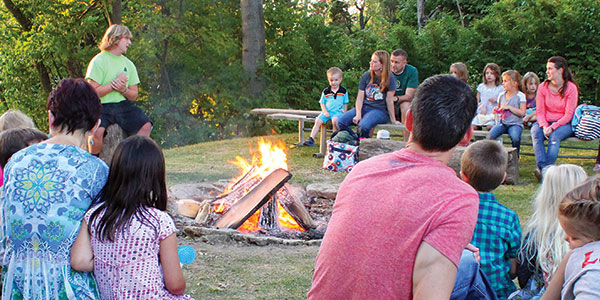 patrons sitting around a campfire listening to stories at Johnson Hills Park