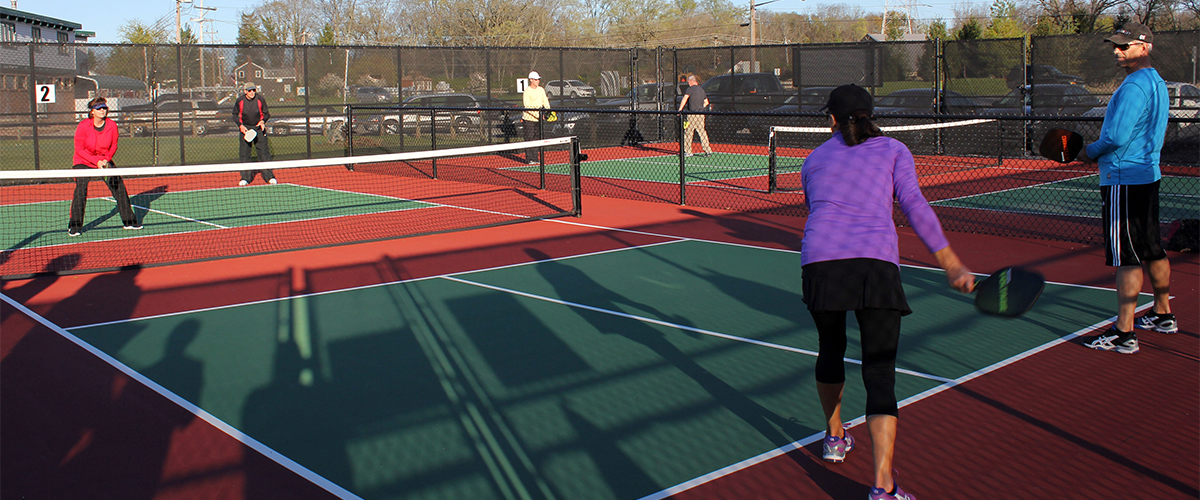 adults playing pickleball on court