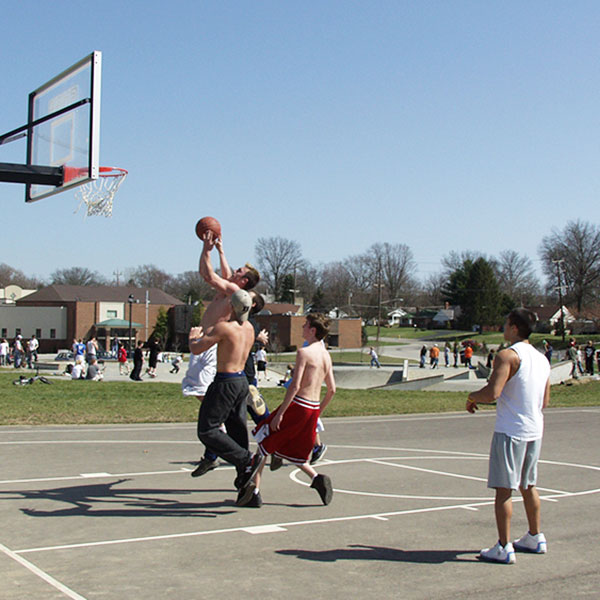 Adult men playing basketball on the courts at Beech Acres Park
