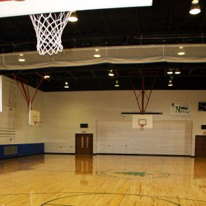 Basketball net in the foreground and view of volleyball curtain and two other basketball courts in the Anderson Parks RecPlex Gym