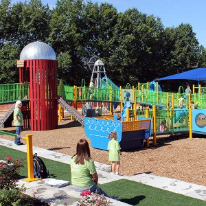 Farm-themed playground that features swings, covered sand area, an array of slides, and jungle gyms.