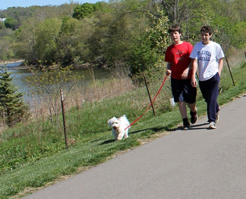two boys walking a dog on the Riverside Park hike/bike trail