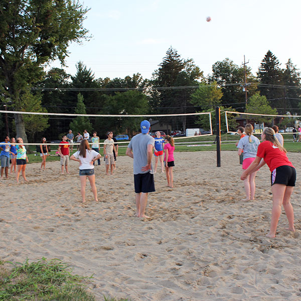 A group of young adults playing an evening game of volleyball on the sand courts at Beech Acres Park