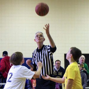 adult referee at a youth basketball game