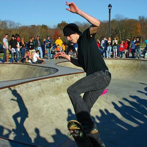 Young man skateboarding in front of a large audience at Beech Acres Park Skatepark