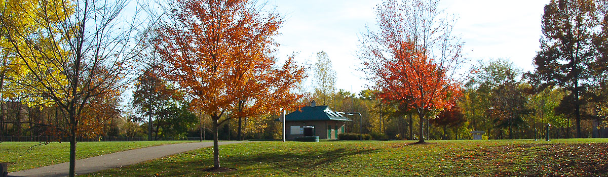 Kellogg Park in the fall with vibrant colored trees and image of restroom building in the background