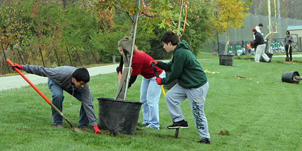 volunteers planting trees at riverside park during Make A Difference Day