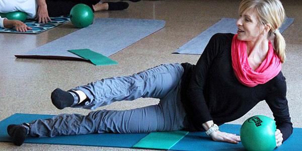 instructor teaching park district pilates mat mix on a mat with a ball