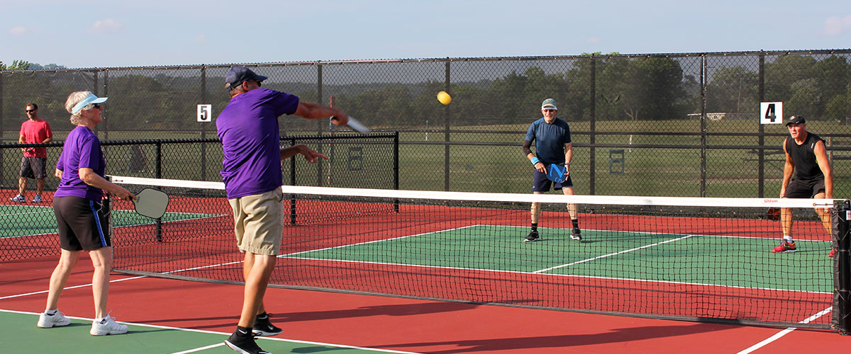 Two teams competing against each other in a pickleball game. Pickleball courts located at Clear Creek Park