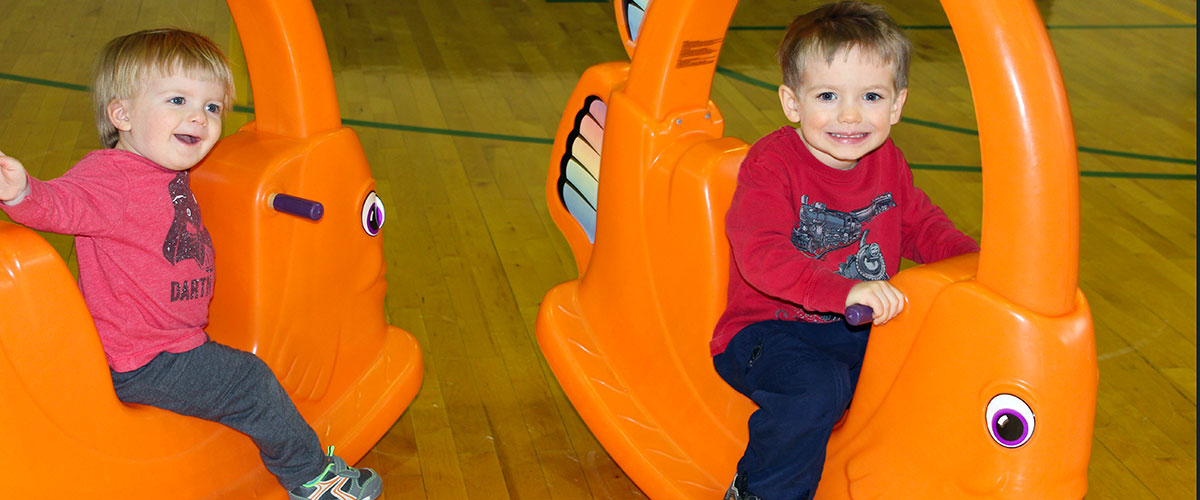 two boys sitting on rocking toys at preschool open gym