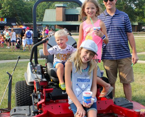 family on a mower at Farmer in the Dell