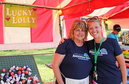 park staff and volunteer smile in front of greater anderson days kids game booth