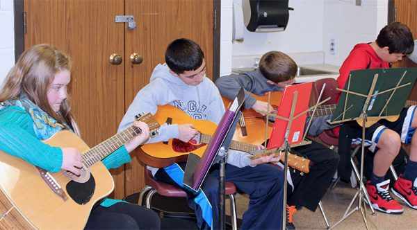 teens learn to play guitar