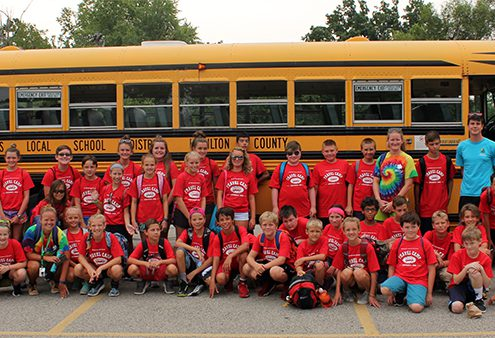 travel campers line up in front of a bus before a field trip