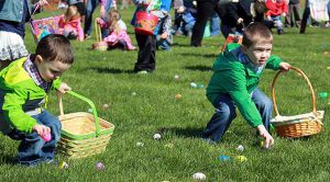 two boys collect eggs at the youth hunts at riverside park