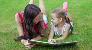 babysitter reads to a young girl