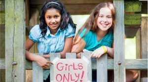 "two girls holding a sign that says ""girls only"". class empowers girls to be self-confident"