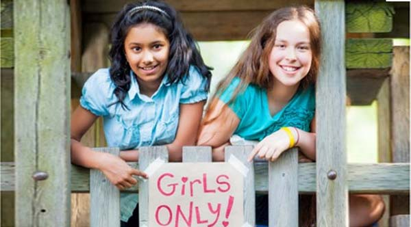 """two girls holding a sign that says """"girls only"""". class empowers girls to be self-confident"""