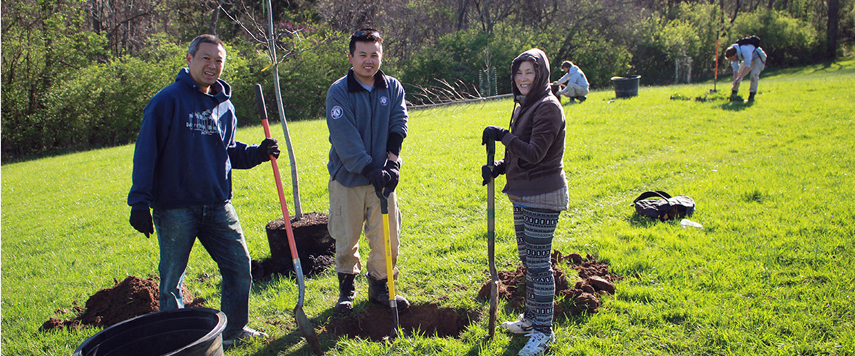 family digging holes to plant trees at annual great american cleanup day