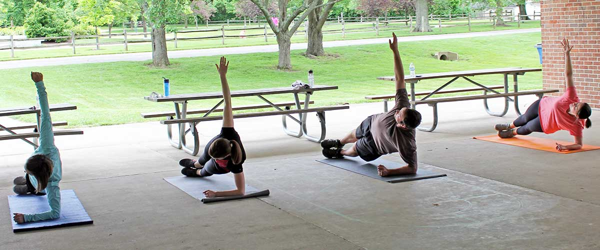 adults performing side plank exercise