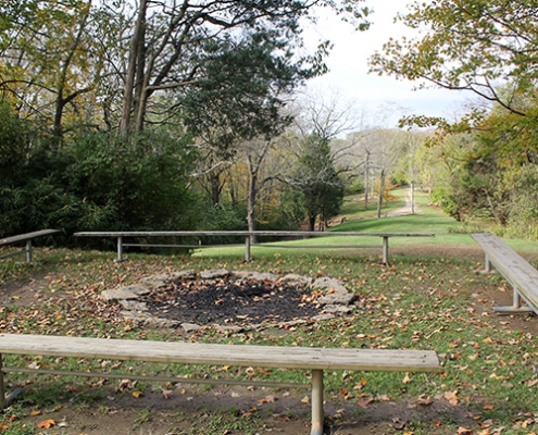 A large fire pit surrounded by benches at Johnson Hills Park