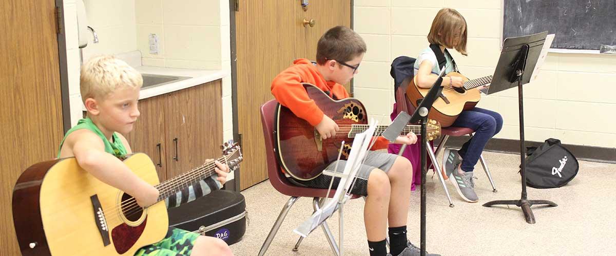 3 children sitting playing guitar