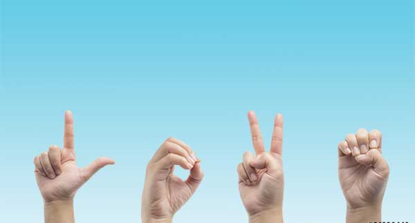 Hands using sign language to spell Love