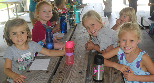 four little girls sitting at a picnic table smiling