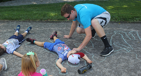 child laying on the grown being traced with sidewalk chalk