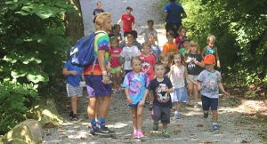 children walking on up a gravel trail with camp counselor
